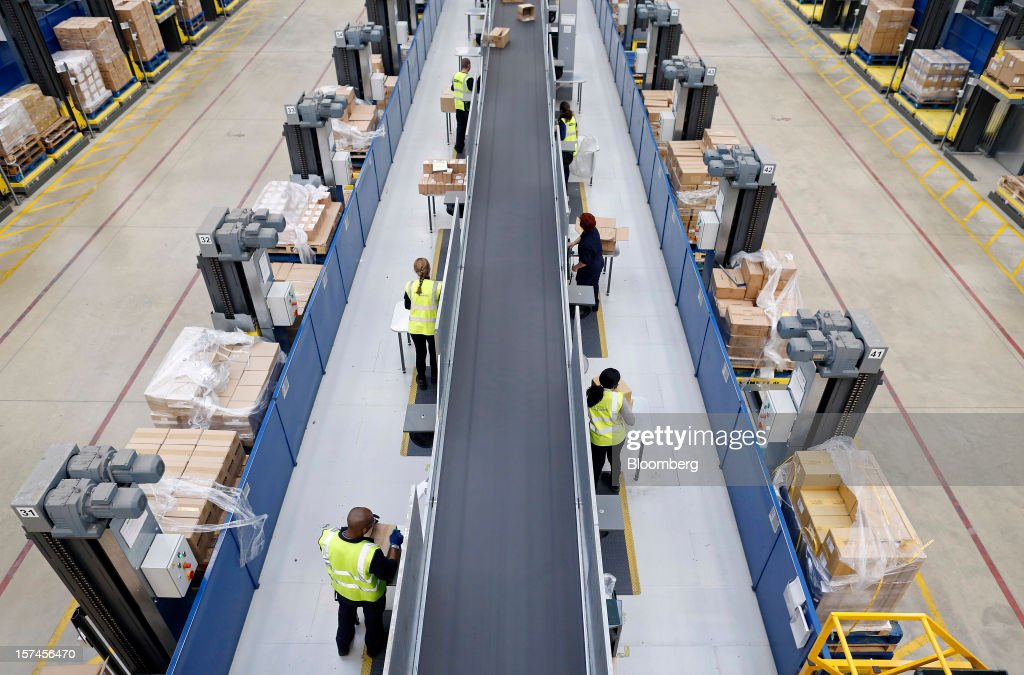 Employees process goods inside John Lewis Plc's semi-automated distribution centre in Milton Keynes, U.K., on Monday, Dec. 3, 2012. An index of U.K. retail sales rose to a five-month high in November, according to a monthly report from the Confederation of British Industry. Photographer: Simon Dawson/Bloomberg via Getty Images