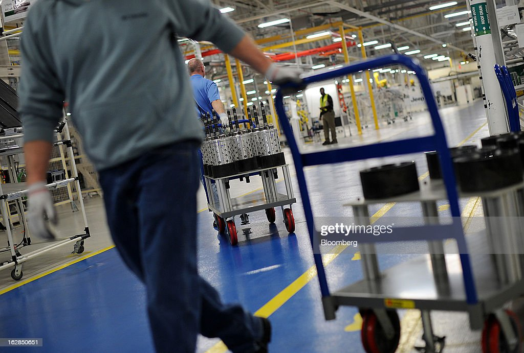 Employees pull carts carrying transmission parts at the Chrysler Group LLC transmission plant in Kokomo, Indiana, U.S., on Thursday, Feb. 28, 2013. Chrysler Group LLC, the automaker majority owned by Fiat SpA, will invest about $374 million and add 1,250 jobs at Indiana factories to boost output of eight-and nine-speed transmissions. Photographer: Daniel Acker/Bloomberg via Getty Images