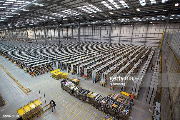 Employees push carts along aisles as they process customer orders ahead of shipping at one of Amazoncom Inc's fulfillment centers in Rugeley UK on...