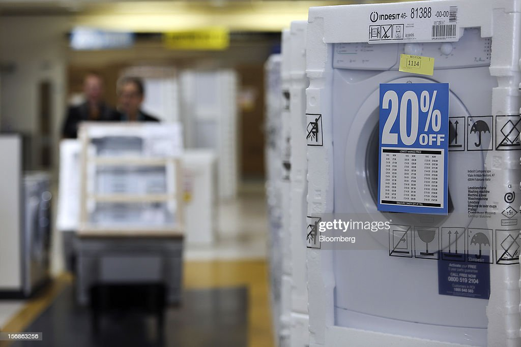 Employees push household appliances past a display of reduced-price Indesit Co SpA washing machines inside a Comet electronics store in Slough, U.K., on Friday, Nov. 23, 2012. Comet, a U.K. electronics chain, appointed Deloitte LLP as insolvency administrator, less than a year after being bought by private-equity firm OpCapita LLP. Photographer: Chris Ratcliffe/Bloomberg via Getty Images