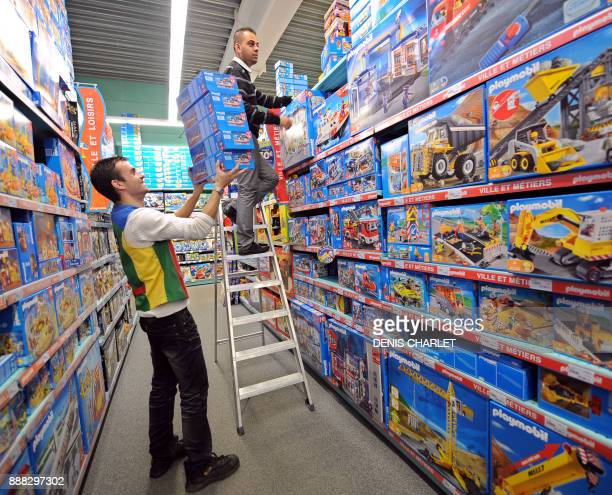 Employees rank boxes in the shelves of La Grande Recre toys departement store in the French northern city of BruaylaBuissiere on November 20 2010 As...