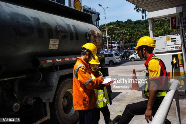 Employees record notes while fuel from a tanker truck is transferred to gas fuel tanks at a Royal Dutch Shell Plc gas station in Kota Kinabalu in...