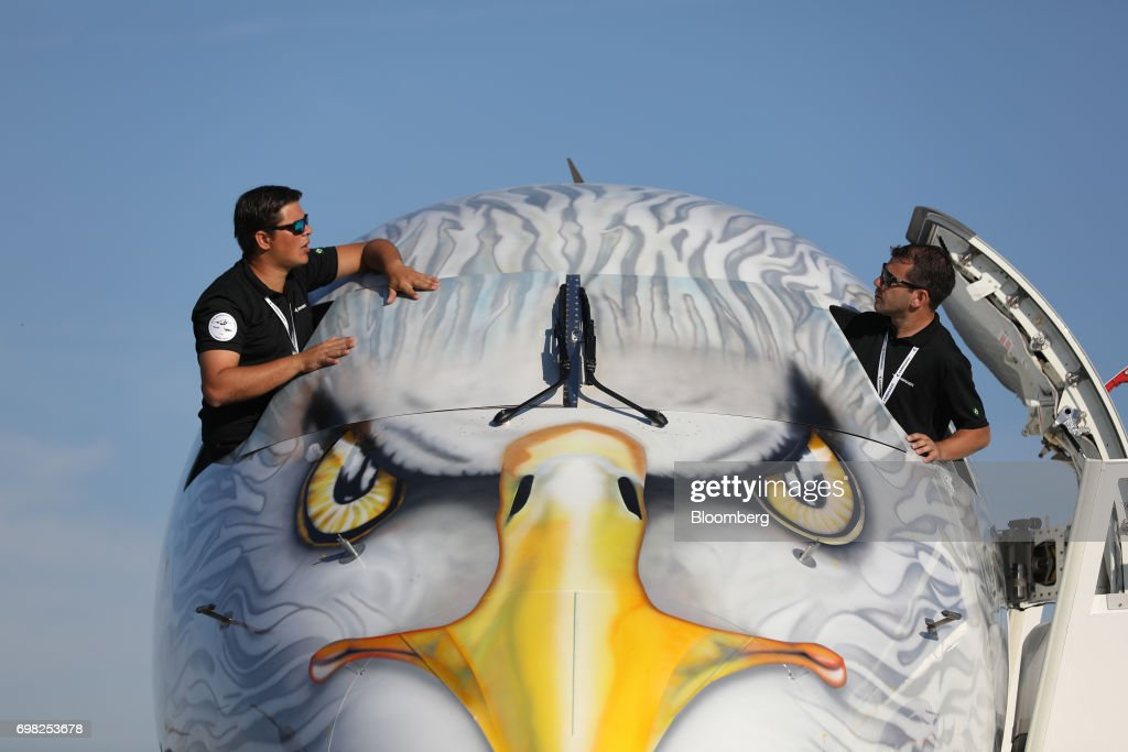 Employees remove cockpit window covers from an Embraer SA E195-E2 aircraft during the 53rd International Paris Air Show at Le Bourget, in Paris, France, on Tuesday, June 20, 2017. The show is the world's largest aviation and space industry exhibition and runs from June 19-25. Photographer: Chris Ratcliffe/Bloomberg via Getty Images