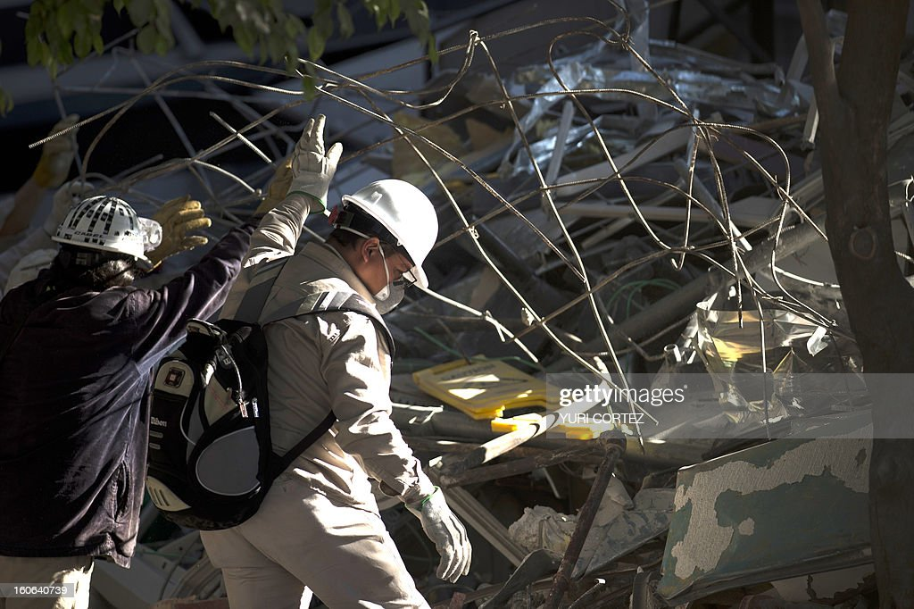 PEMEX employees remove debris at the building of state-owned Mexican oil giant Pemex, in Mexico City on February 4, 2013. An explosion rocked the skyscraper, last week, leaving up to 36 dead and 121 injured. AFP PHOTO/ YURI CORTEZ