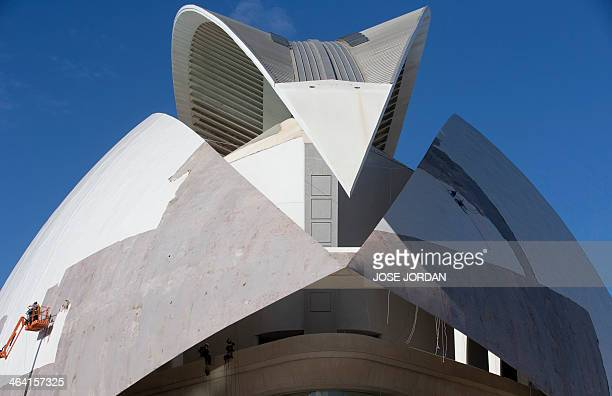 Employees remove the ceramic mosaic facade covering the roof of the 'Palau de les Arts Reina Sofia' part of the City of Arts and Science in Valencia...