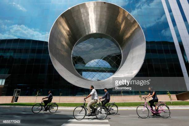 Employees ride a bicycles past Building 44 at the Infosys Ltd campus in Electronics City in Bangalore India on Monday Jan 27 2013 Infosys India's...
