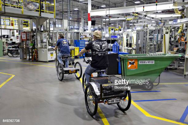 Employees ride trycicles through the HarleyDavidson Inc powertrain operations facility in Menomonee Falls Wisconsin US on Monday Sept 18 2017 The US...