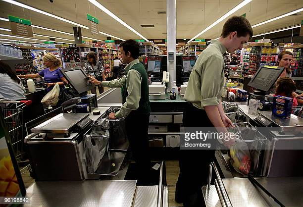 Employees ring through customers' purchases at the checkout counter at a Woolworths Ltd supermarket in Melbourne Australia on Wednesday Jan 27 2010...