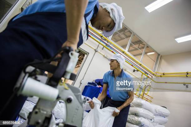 Employees seal and stack bags of garlic at the Nithi Foods Co factory in the San Pa Tong district of Chiang Mai Thailand on Tuesday May 23 2017...