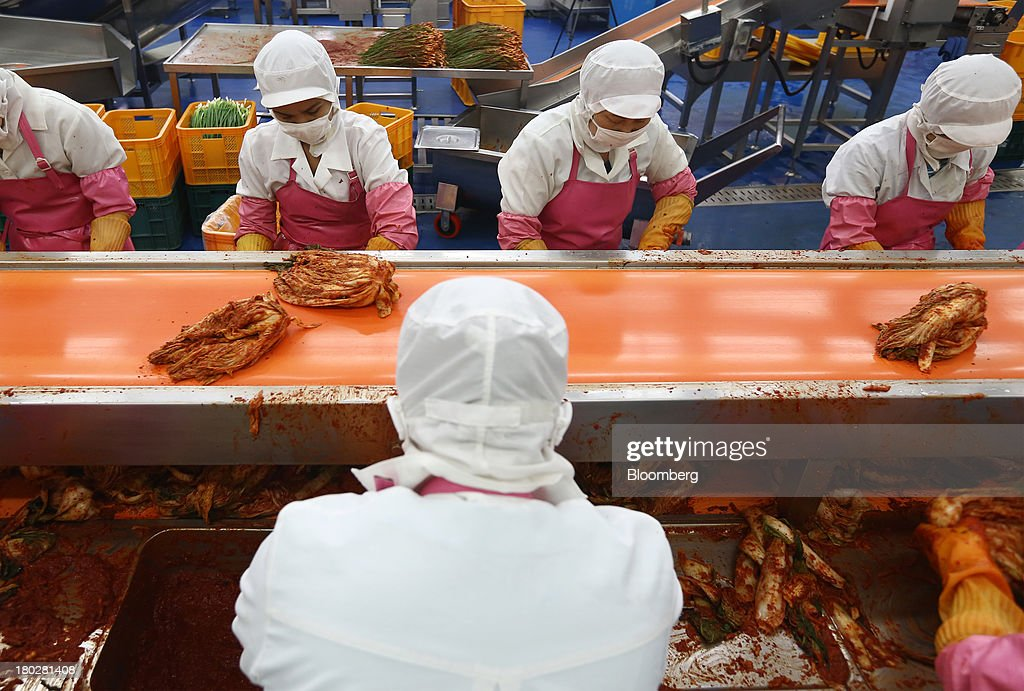 Employees season kimchi on the production line at the Gamchilbaegi Co. kimchi factory in Gwangju, South Korea, on Tuesday, Sept. 10, 2013. Gross domestic product rose 1.1 percent in the second quarter from the preceding three months, the most in more than two years, central bank data showed Sept. 5. Photographer: SeongJoon Cho/Bloomberg via Getty Images