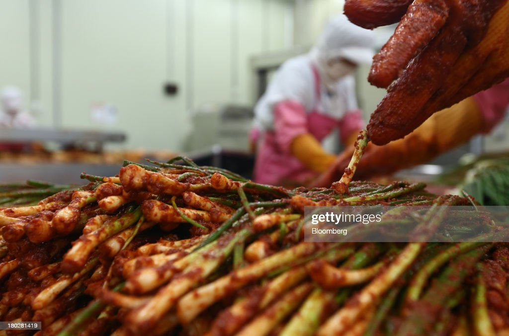 Employees season scallion kimchi on the production line at the Gamchilbaegi Co. kimchi factory in Gwangju, South Korea, on Tuesday, Sept. 10, 2013. Gross domestic product rose 1.1 percent in the second quarter from the preceding three months, the most in more than two years, central bank data showed Sept. 5. Photographer: SeongJoon Cho/Bloomberg via Getty Images