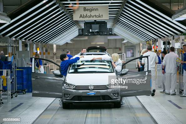 Employees secure protective covers to a Volkswagen Golf automobile following final quality checks on the production line at the Volkswagen AG factory...