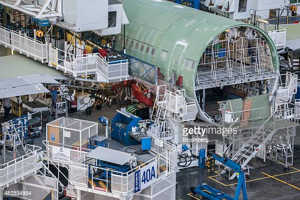 Employees secure wing sections to an Airbus A330 aircraft fuselage on the assembly line in the Airbus Group NV factory in Toulouse France on Friday...