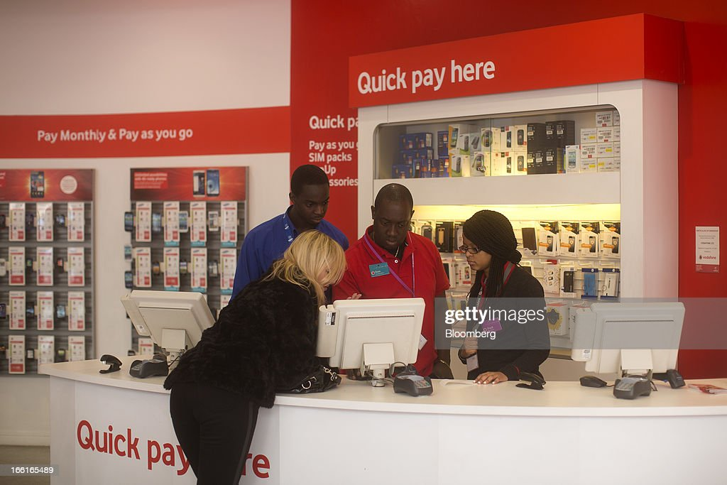Employees serve a customer at a service desk inside Vodafone Group Plc's Oxford Street store in London, U.K., on Monday, April 8, 2013. Vodafone Group Plc is restating its results going back two fiscal years as new international accounting rules for joint ventures cut historical revenue and earnings. Photographer: Simon Dawson/Bloomberg via Getty Images