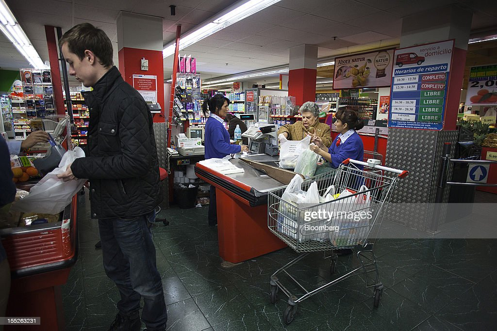 Employees serve customers at the checkout counter of an Eroski Group supermarket in Madrid, Spain, on Friday, Nov. 2, 2012. Spain is unlikely to need a full bailout while any request from the euro area's fourth-largest economy for alternative support measures must be met with a swift response, Finnish Prime Minister Jyrki Katainen said. Photographer: Angel Navarrete/Bloomberg via Getty Images