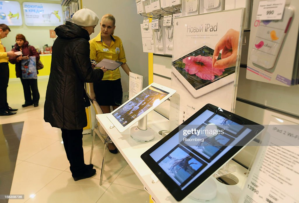 Employees serve customers near a promotional display of Apple Inc. iPad tablets inside a Euroset Holding NV mobile phone store in Moscow, Russia, on Thursday, Dec. 13, 2012. OAO MegaFon and its main shareholder billionaire Alisher Usmanov bought 50 percent of Euroset Holding NV in a deal that gives Russia's biggest handset retailer an enterprise value of $2.3 billion. Photographer: Andrey Rudakov/Bloomberg via Getty Images