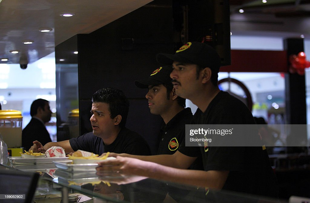 Employees serve up orders at a Fatburger outlet in Karachi, Pakistan, on Saturday, Jan. 5, 2013. Fatburger opened its first outlet in Pakistan to the public on Jan. 5. Photographer: Asim Hafeez/Bloomberg via Getty Images