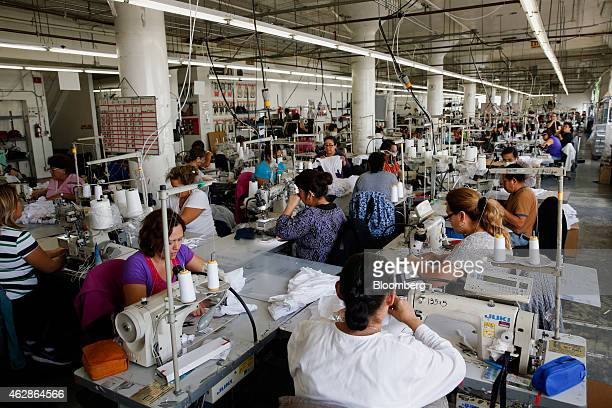 Employees sew garments at the American Apparel Inc factory in downtown Los Angeles California US on Wednesday Feb 4 2015 The company's spring...