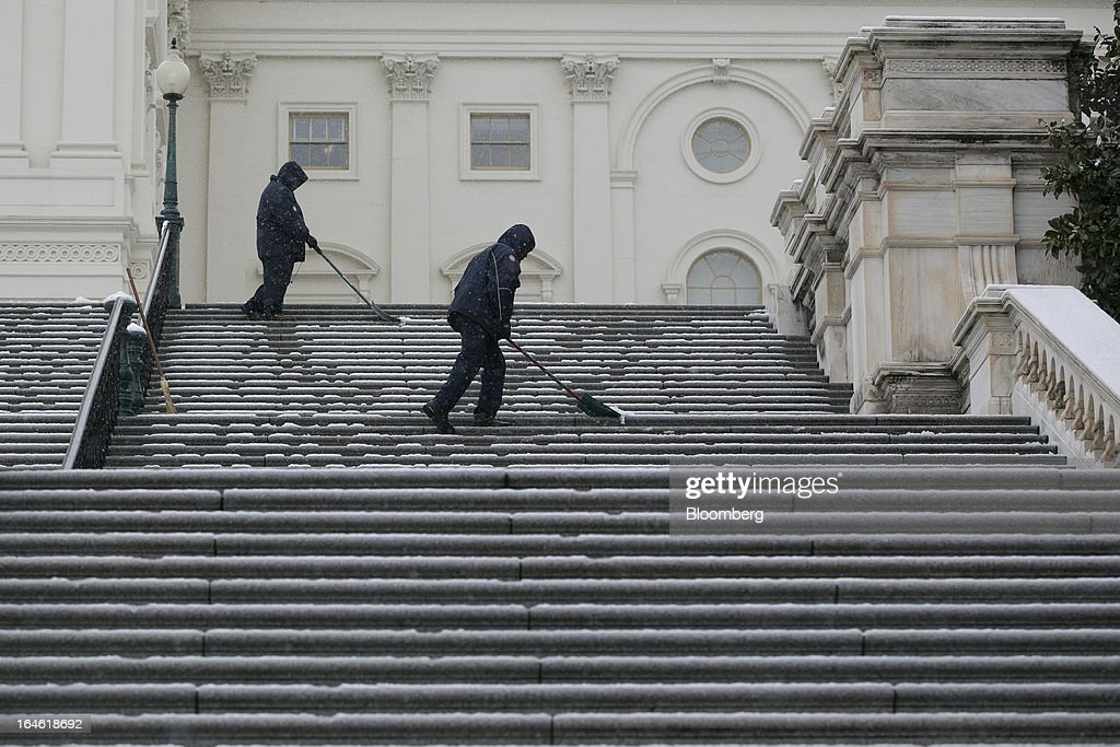Employees shovel the steps outside the U.S. Capitol in Washington, D.C., U.S., on Monday, March 25, 2013. An early spring snowstorm tied up air traffic along the U.S. East Coast, threatening to bring 3 inches (7.6 centimeters) of slushy snow to the large cities from Washington to New York. Photographer: Andrew Harrer/Bloomberg via Getty Images