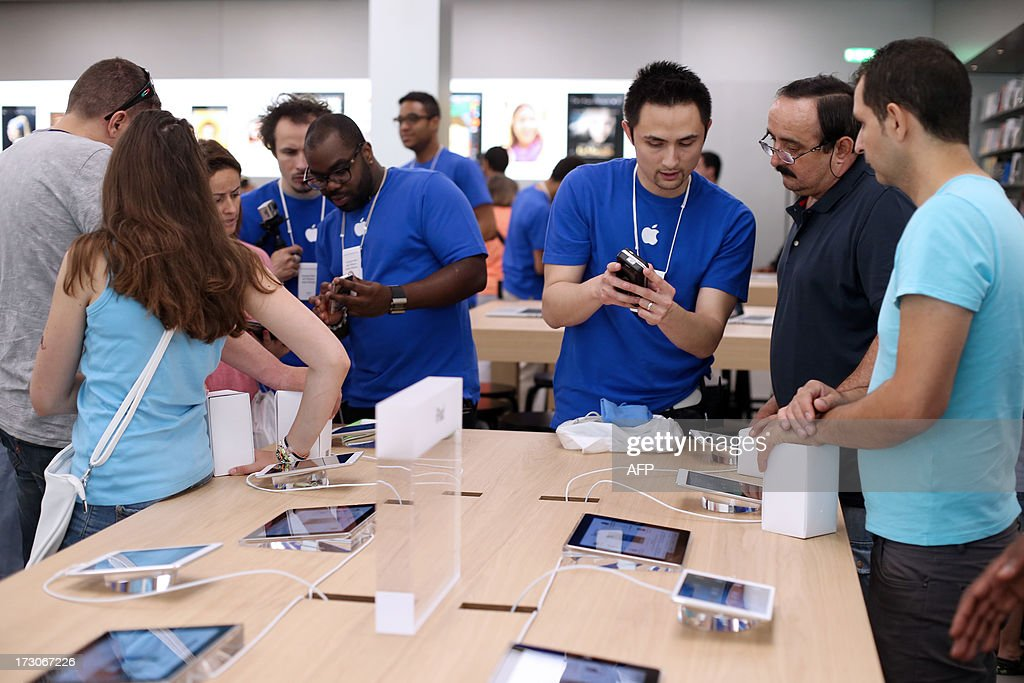 Employees show to customers Apple's iPhone 5 smartphones over iPads in a new Apple store on July 6, 2013 in Rosny-sous-Bois, near Paris.