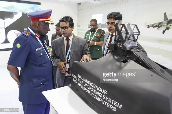 Employees shows an attendee a Hindustan Aeronautics Ltd Real Time Operating System for airborne computers at the company's booth during the Aero...