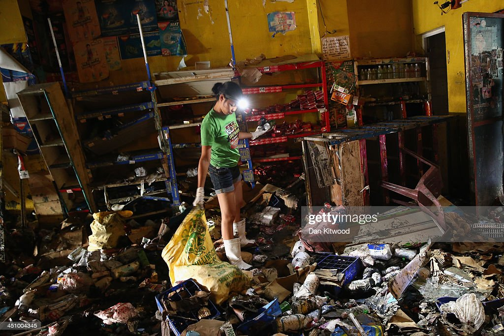 Employees sift through rubbish looking for retrievable items at the Nena's Trading store on November 21, 2013 in Leyte, Philippines. Typhoon Haiyan which ripped through Philippines over a week ago has been described as one of the most powerful typhoons ever to hit land, leaving thousands dead and hundreds of thousands homeless. Countries all over the world have pledged relief aid to help support those affected by the typhoon however damage to the airport and roads have made moving the aid into the most affected areas very difficult. With dead bodies left out in the open air and very limited food, water and shelter, health concerns are growing.