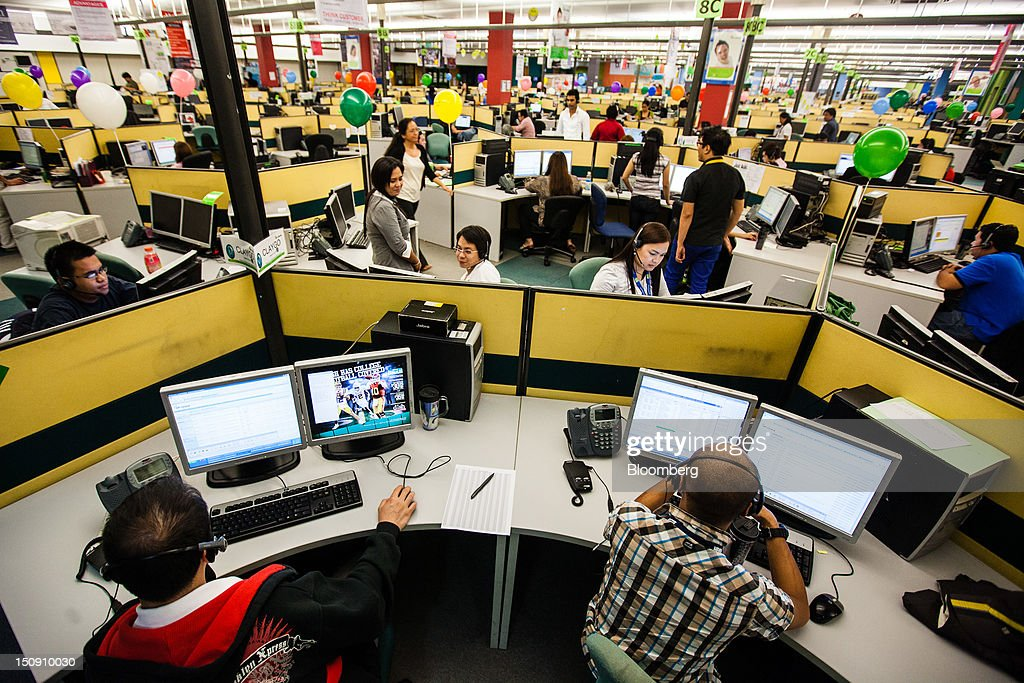 Employees sit in front of computer screens as they work in an SPi Global call center in Manila the Philippines on Tuesday Aug 28 2012 Manilabased SPi...