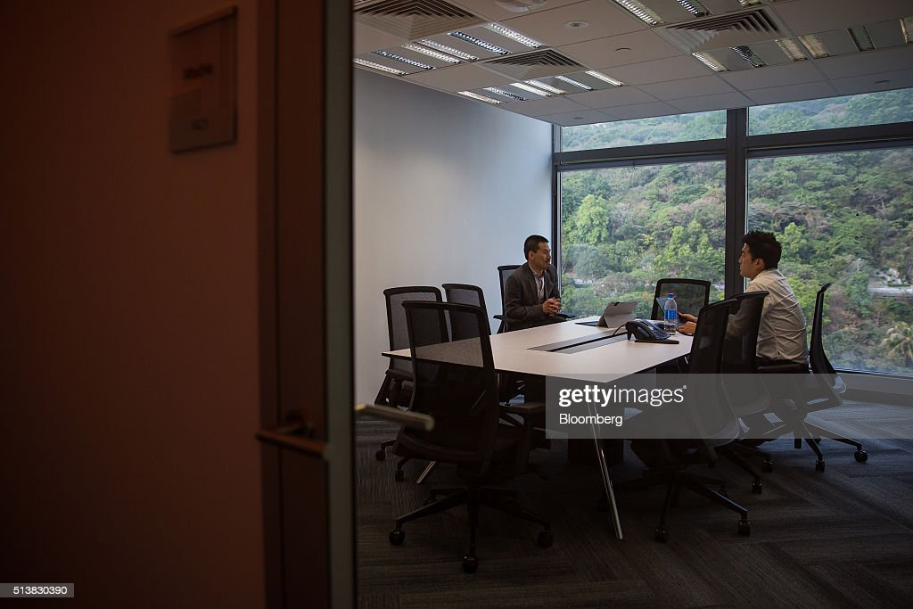 Employees sit inside a meeting room at the Microsoft Corp. Office and Experience Center during a media event for the opening of the workspace in Hong Kong, China, on Friday, March 4, 2016. Microsoft is rolling out a new service for its Windows 10 operating system to help large businesses detect hackers, security threats and unusual behavior on their networks, rivaling companies like FireEye Inc. and Symantec Corp. Photographer: Billy H.C. Kwok/Bloomberg via Getty Images