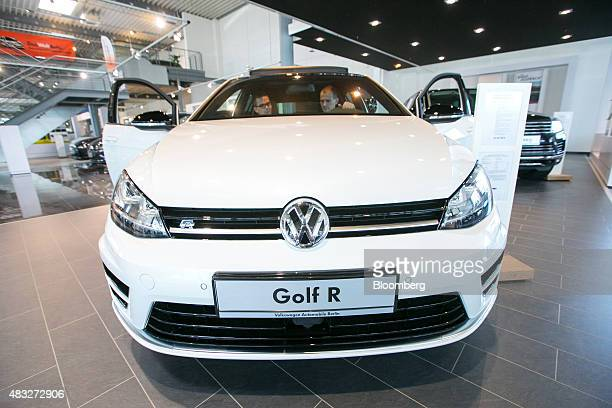 Employees sit inside a Volkswagen Golf R automobile in the used car sales area of the Volkswagen AG showroom in Berlin Germany on Thursday Aug 6 2015...
