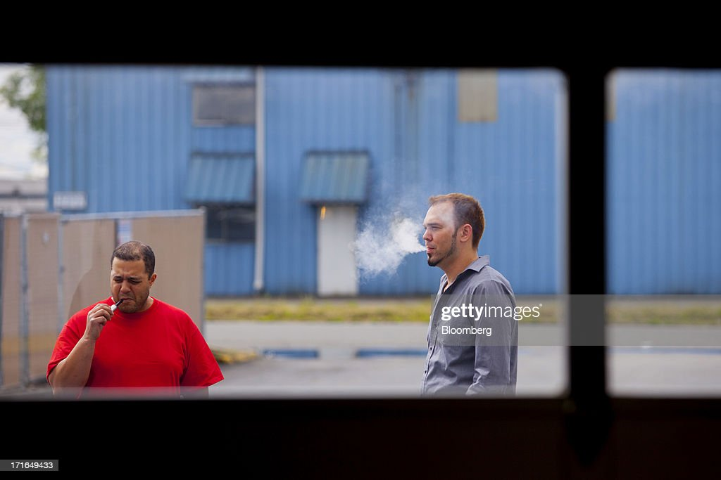 Employees smoke electronic cigarettes while on break at the ProVape Inc. facility in Monroe, Washington, U.S., on Wednesday, June 26, 2013. U.S. sales of electronic cigarettes are estimated to double in 2013 from last year, to $1 billion, according to estimates made by the Tobacco Merchants Association (TMA) and Mintel. Photographer: Mike Kane/Bloomberg via Getty Images
