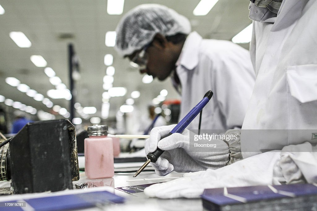 Employees solder solar cells at a tabbing station on the solar photovoltaic module production line at the Tata Power Solar Systems Ltd. manufacturing plant in Bangalore, India, on Tuesday, June 11, 2013. Tata Groups solar unit is expanding its business building plants for customers, forecasting that offices and factories will be paying more for grid power than solar by 2016 in most Indian states. Photographer: Dhiraj Singh/Bloomberg via Getty Images