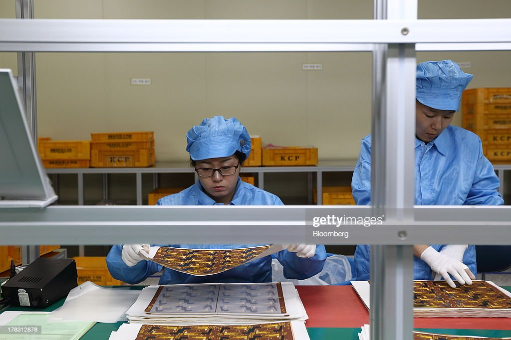 Employees sort Flexible Printed Circuit Board (F-PCB) panels on the production line at the Seil Electronics Co. factory in Incheon, South Korea, on Wednesday, Aug. 28, 2013. South Korea has surpassed Brazil, Russia and India to become the second-biggest emerging stock market for the first time since 2006, as a stable won and record current-account surplus lure investors. Photographer: SeongJoon Cho/Bloomberg via Getty Images