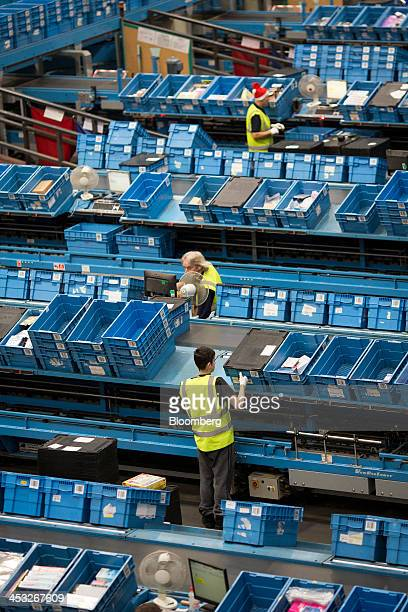 Employees sort goods as they arrive in crates to be processed as customer orders at an Argos goods distribution center operated by Home Retail Group...