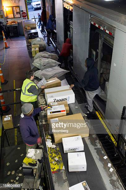 Employees sort through packages as they are offloaded at a United Parcel Service Inc sorting facility in San Francisco California US on Thursday Dec...