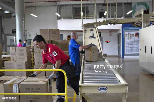Employees stack boxes coming off a conveyor belt for shipment at the Philip Morris International Coltabaco SAS production facility in Medellin...