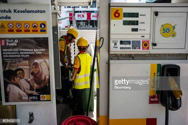 Employees stand as fuel from a tanker truck is transferred to gas fuel tanks at a Royal Dutch Shell Plc gas station in Kota Kinabalu in Sabah...