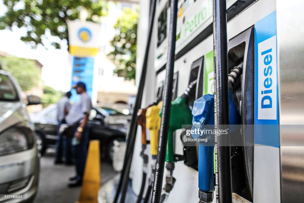 Employees stand at a Bharat Petroleum Corp. gas station in Mumbai, India, on Wednesday, Aug. 21, 2013. The prospect of an indecisive 2014 election in India is eroding confidence among global investors that the government can stop the rupees worst drop in more than two decades. Photographer: Dhiraj Singh/Bloomberg via Getty Images