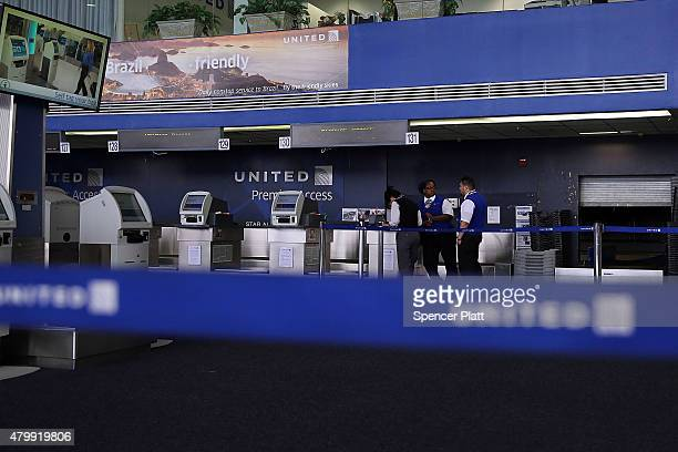 Employees stand at the United Airlines terminal at Newark Liberty Airport on July 8 2015 in Newark New Jersey A computer system glitch caused...