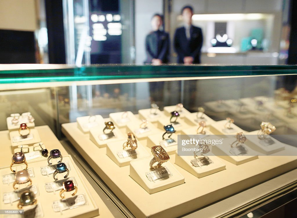Employees stand behind jewel-encrusted gold rings displayed at the Chow Sang Sang Holdings International Ltd. jewelry store in the Sanlitun district of Beijing, China, on Monday, March 11, 2013. China's consumer prices climbed 3.2 percent from a year earlier, according to figures released March 9, exceeding January's 2 percent gain and the median estimate for a 3 percent increase in a Bloomberg survey of analysts. Photographer: Tomohiro Ohsumi/Bloomberg via Getty Images