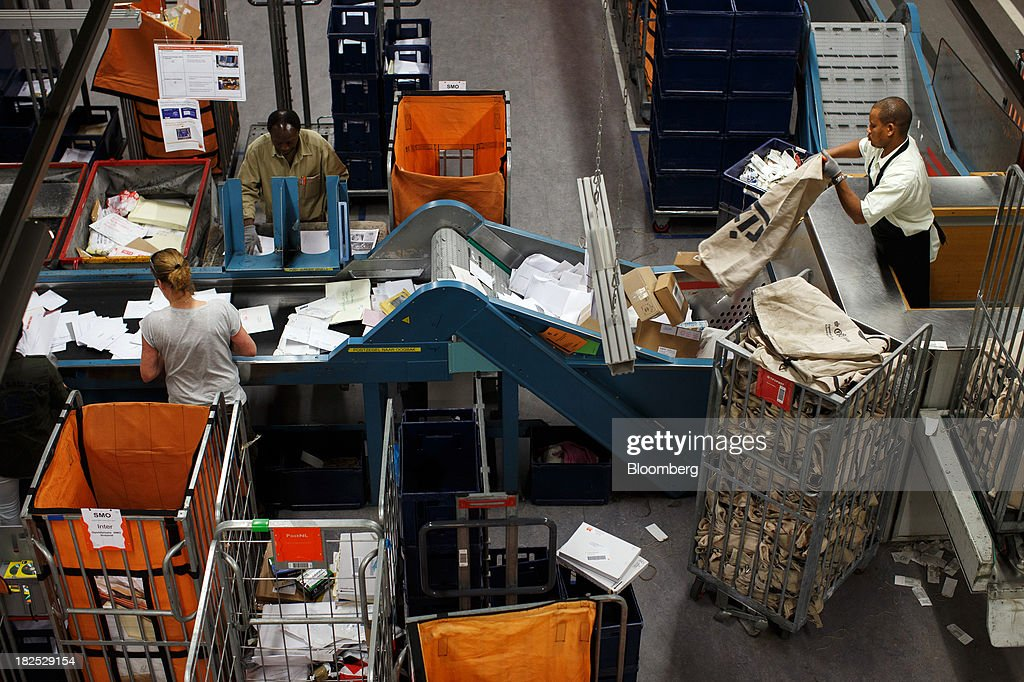 Employees stand beside a conveyor belt as letters and packages are sorted at the PostNL NV mail sorting center in Nieuwegein, Netherlands, on Friday, Sept. 27, 2013. PostNL NV rose the most in two months on Sept. 19 after the Dutch postal operator raised its full-year forecast and announced higher prices for stamps. Photographer: Jasper Juinen/Bloomberg via Getty Images