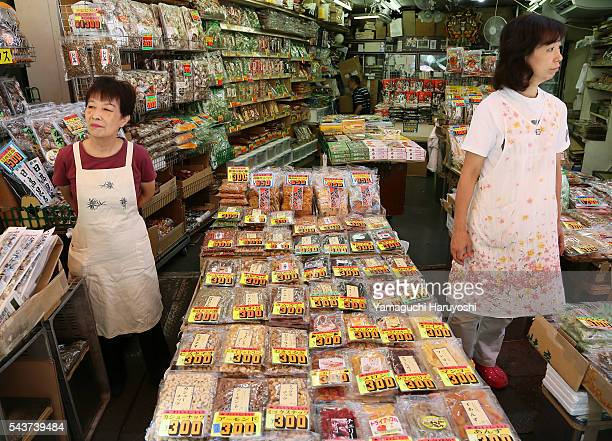 Employees stand beside Dried food and spices in a shop at Ameyoko market in Tokyo Japan Sep 2013 Ameyoko is a bustling outdoor marketplace and...