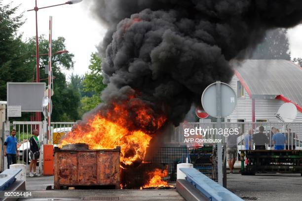 Employees stand by a fire of burning tyres outside the plant of the GMS company on June 27 2017 in La Souterraine central France Around 280 jobs are...