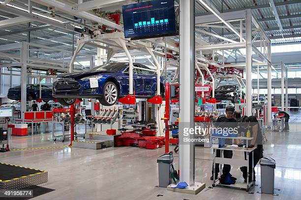 Employees stand by a work bench as Tesla Model S automobiles stand on raised cradles on the battery pack and driving unit assembly line at the Tesla...