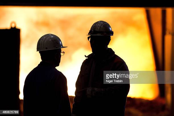 Employees stand in front of the blast furnace of German steel manufacturer Salzgitter AG on March 25 2014 in Salzgitter Germany Salzgitter AG is one...