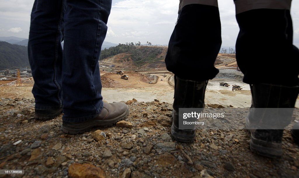 Employees stand in front of the open pit of the G-Resources Group Ltd. Martabe gold and silver mine in Batang Toru, North Sumatra province, Indonesia, on Tuesday, Feb. 12, 2013. G-Resources is scheduled to announce financial results on Feb. 28. Photographer: Dadang Tri/Bloomberg via Getty Images