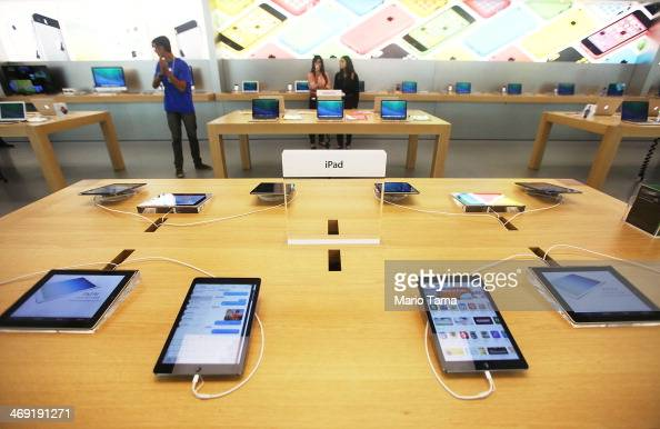 Employees stand inside Brazil's first Apple retail store in the Village Mall shopping center during a press preview on February 13 2014 in Rio de...
