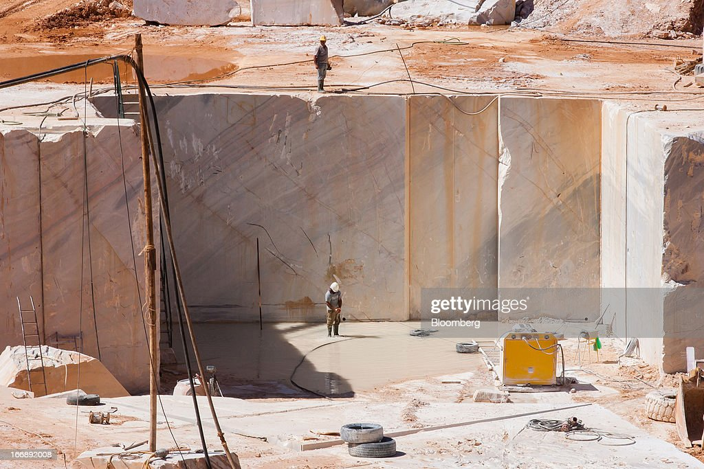 Employees stand on raw marble during excavation in a quarry pit operated by Bloco B in Bencatel, Vila Vicosa, Portugal, on Wednesday, April 17, 2013. Portugal is posting its first trade surplus in at least six decades, which may help vindicate a strategy of front-loading austerity to deliver economic reform. Photographer: Mario Proenca/Bloomberg via Getty Images