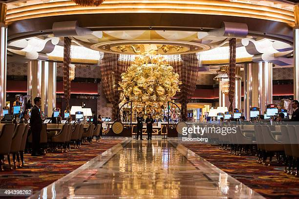 Employees stand on the gaming floor of the casino at the Studio City casino resort developed by Melco Crown Entertainment Ltd ahead of the grand...
