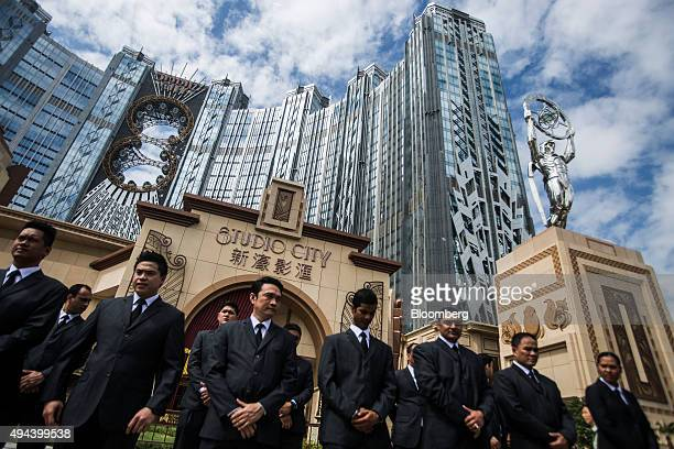 Employees stand outside the Studio City casino resort developed by Melco Crown Entertainment Ltd in Macau China on Tuesday Oct 27 2015 Studio City...