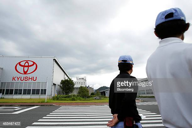 Employees stand outside the Toyota Motor Kyushu Inc plant in Kanda Fukuoka Prefecture Japan on Thursday Aug 7 2014 Toyota's Lexus luxury brand last...